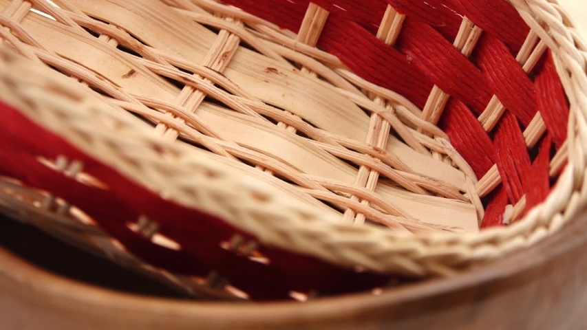 Straw basket lying in a wooden bowl. they rotate on a cutting board. | Shutterstock HD Video #1051989643