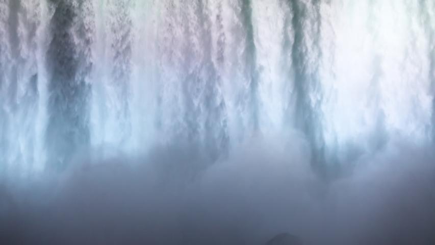NIAGARA FALLS, NEW YORK - 8 AUG 2019: Niagara Falls night flow brink waterfall multi colored lights 60 fps. International border USA New York and Canadian Ontario. honeymoon vacation destination.