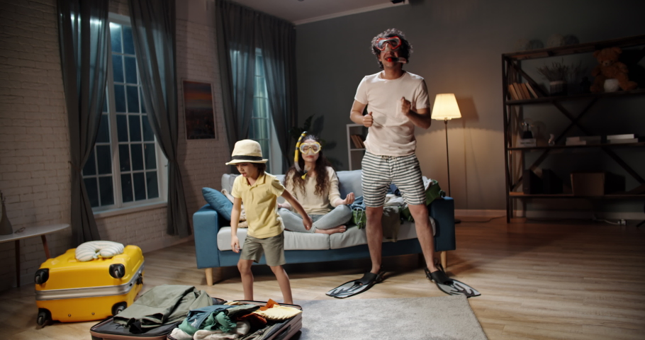 Funny asian family of three happy about upcoming vacation. Mother wearing scuba diver mask meditating while husband and kid are dancing near suitcases - travelling, happy family 4k footage Royalty-Free Stock Footage #1051998010