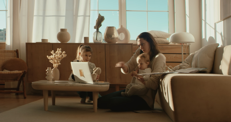 Mother working from home, making a work call surrounded by her daughters.. Shot on RED Dragon | Shutterstock HD Video #1052014417