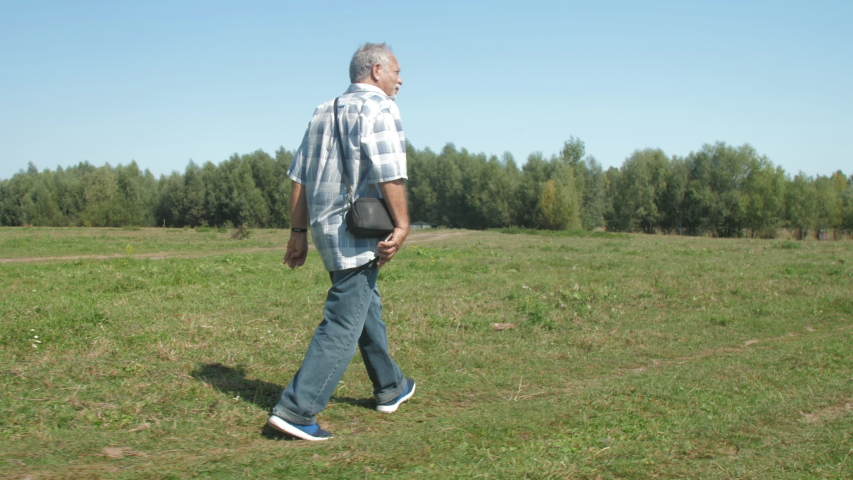 Active pensioner with grey beard in jeans walks along green lawn actively against lush forest and clear sky slow motion. Concept people environment   Shutterstock HD Video #1052025283