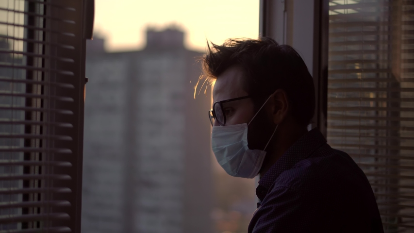 Sad Man In Face Mask Looking Through Window.Lockdown Stay At Home.Stay Home Self Isolation Coronavirus Covid-19 Pandemic Quarantine Protection.Man In Face Mask In Quarantine Self Isolation Lockdown.