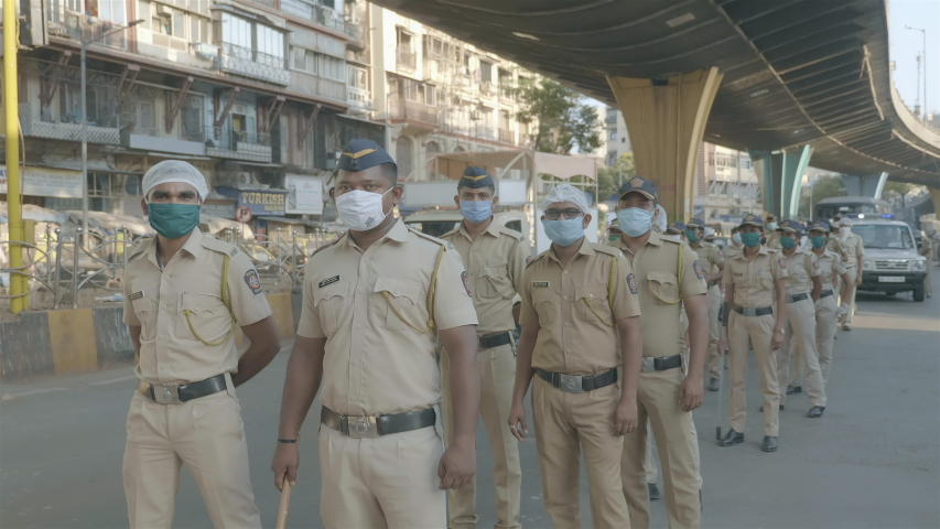 A group of men/ male police force/ constables/ personals wearing face masks standing on the road conducting  public awareness rally during Covid19/ Coronavirus pandemic , Mumbai, India (April 2020)