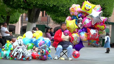 Morelia, Michoacán / Mexico - January 21 2011: Female Street Vendor Sells Animal Shaped Balloons in the Grass in a Public Park whit Trees in the Background