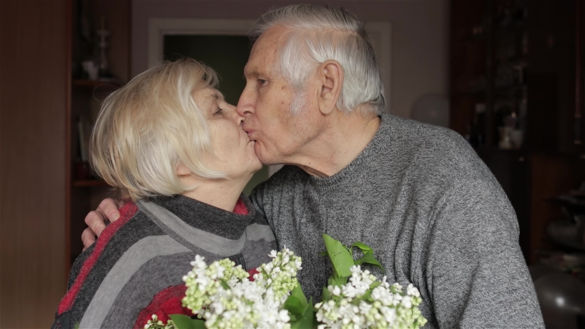 Portrait of a cheerful old elderly happy grandfather and grandmother at home. Grandpa with flowers comes to gandma and making a kiss. Beautiful husband and wife in love. Senior retired grandparents Royalty-Free Stock Footage #1052038264