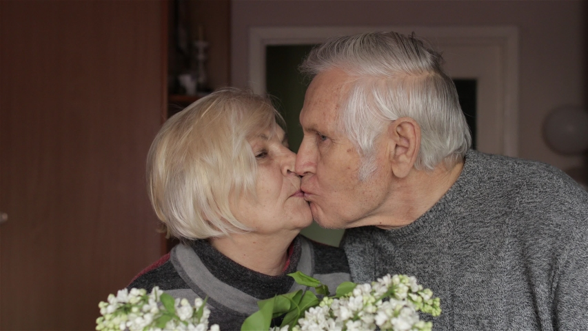 Portrait of a cheerful old elderly happy grandfather and grandmother who smiling and looks at camera at home. Beautiful husband and wife in love. Grandma kissing gandpa. Senior retired grandparents Royalty-Free Stock Footage #1052038273