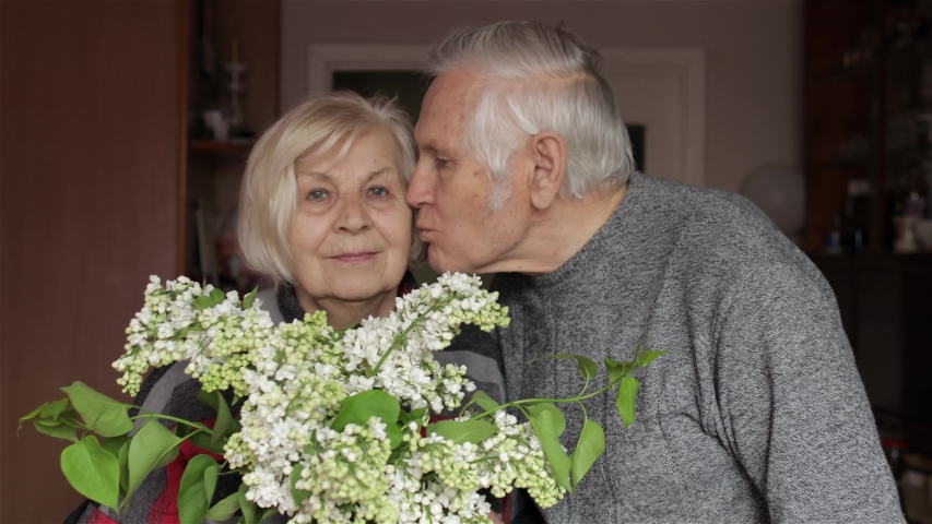 Portrait of a cheerful old elderly happy grandfather and grandmother with flowers at home. Grandpa comes to gandma and making a kiss. Beautiful husband and wife in love. Senior retired grandparents Royalty-Free Stock Footage #1052038276