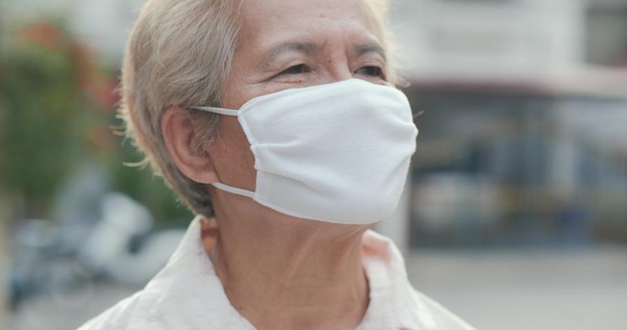 Portrait of senior woman wearing mask to protect herself from virus. N1H1 coronavirus quarantine, virus protection | Shutterstock HD Video #1052049277