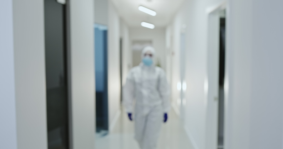 Dedicated female medic in protective suit and glasses working with patients coronavirus infected walking along clinic corridor | Shutterstock HD Video #1052053801