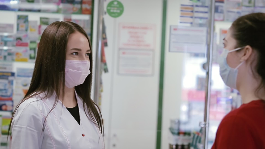 Pharmacist and customer communicate in the pharmacy. Women in medical masks. View from over the buyer's shoulder. Concept of a viral pandemic and protection against infection | Shutterstock HD Video #1052065165