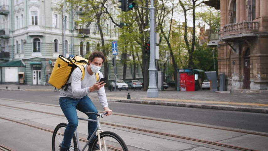 Poartrait of courier with yellow backpack and protective mask rides a bicycle on the street through the city with food delivery and using smartphone | Shutterstock HD Video #1052090803