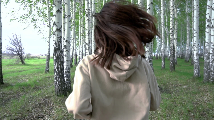 A young woman runs through a birch forest in slow motion. The girl runs between the trees. Back view. Royalty-Free Stock Footage #1052095027