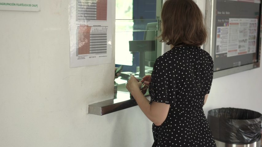 Woman buying a ticket at ticket office at train station paying cash | Shutterstock HD Video #1052095093