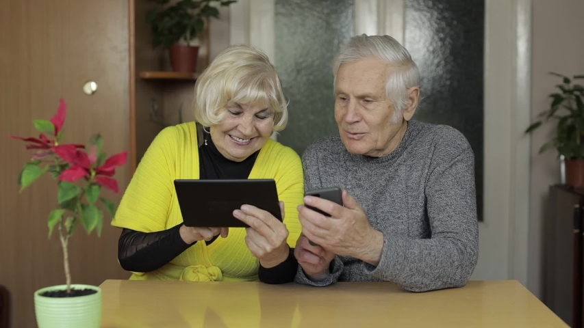 Happy old mature retired couple holding smartphone and tablet looking at cellphone screen watching funny photos sit on table at home. Senior grandparents family having fun enjoy online shopping, news