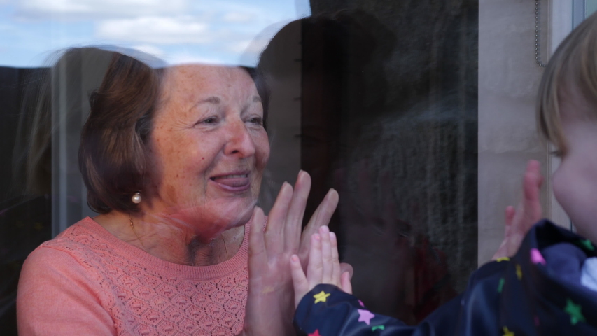 4K: Grandmother seeing her Granddaughter through the window during Lockdown - Social Distancing during the COVID-19 Coronavirus Outbreak. Stock Video Clip Footage