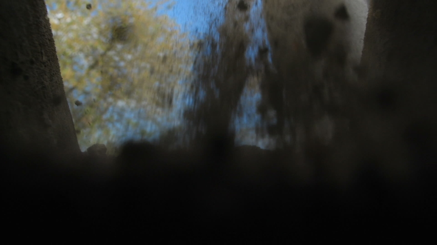 An unrecognizable person in dark clothes is digging a square pit against a blue sky with clouds. Point of view from the grave into which soil is sprinkled from a shovel. Slow motion Royalty-Free Stock Footage #1052102917