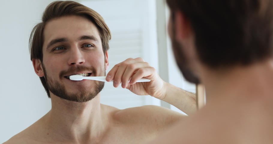 Handsome young man holding toothbrush brushing healthy white teeth looking in bathroom mirror. Charming guy cleaning mouth doing oral cavity morning dental care routine to prevent caries concept. Royalty-Free Stock Footage #1052103028