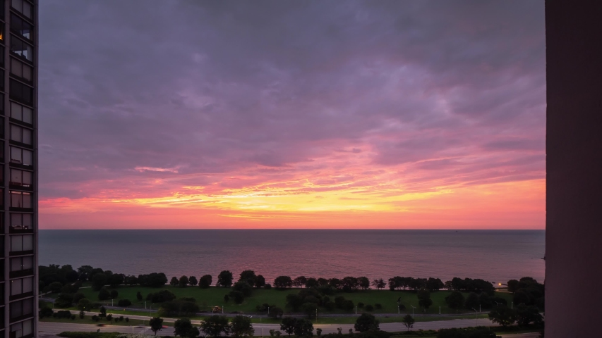 An incredible aerial timelapse of a yellow pink purple and blue sunrise reflects on the water of Lake Michigan as it rises over the horizon with traffic zooming by on Lake Shore Drive below.