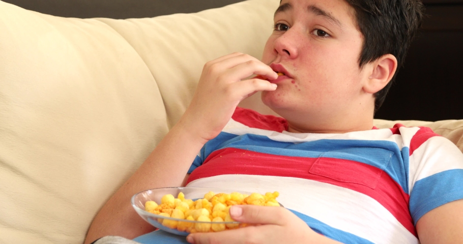 Adolescent boy with acne pimples on the face lying on couch watching tv and eating oily and fryed snacks