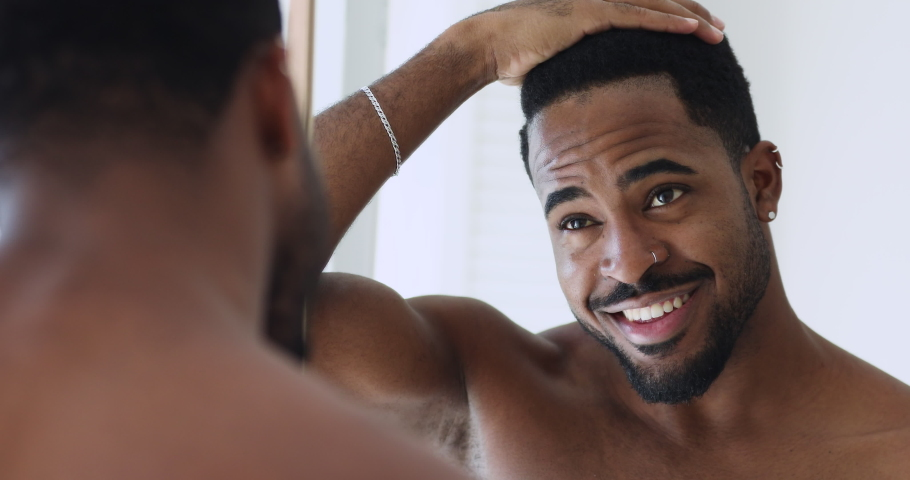 Happy confident afro american hipster guy doing hairstyle looking in mirror. Smiling sexy bare african young man enjoying anti-dandruff shampoo hair result in the morning, grooming stand in bathroom.