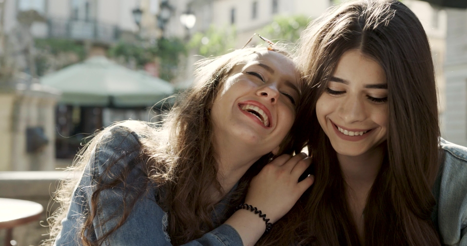 Close-up photo of laughing woman friends hugging each other on city street. Two pretty smiling girls sitting together and hugging at cafe outdoors. Royalty-Free Stock Footage #1052122279