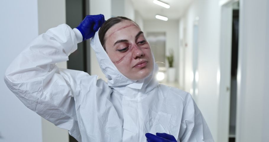 Tired female health worker with face scars from protective uniform taking off hood after overwork with patients coronavirus infected in modern hospital | Shutterstock HD Video #1052122567