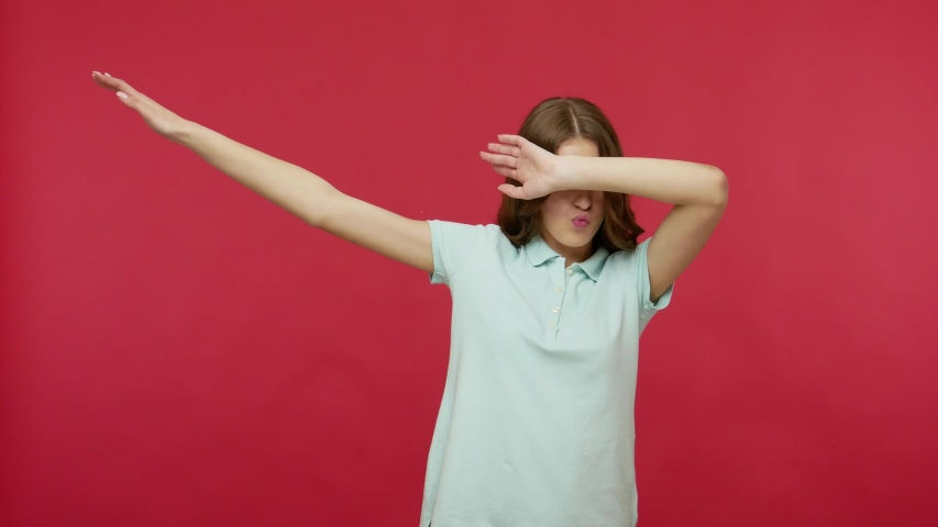 Happy joyful young woman in polo t-shirt celebrating success with dab dance move, famous internet meme of triumph, performing dabbing trends. youth. indoor studio shot isolated on red background   Shutterstock HD Video #1052143975