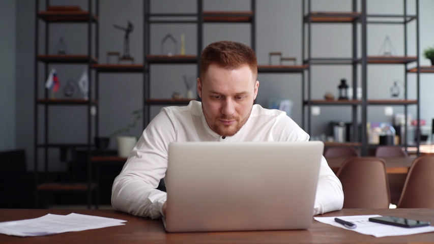 Handsome bearded young businessman wearing fashion casual clothing is typing on laptop computer at the desk in modern office room. Concept of office working. Shotting in slow motion, | Shutterstock HD Video #1052148151