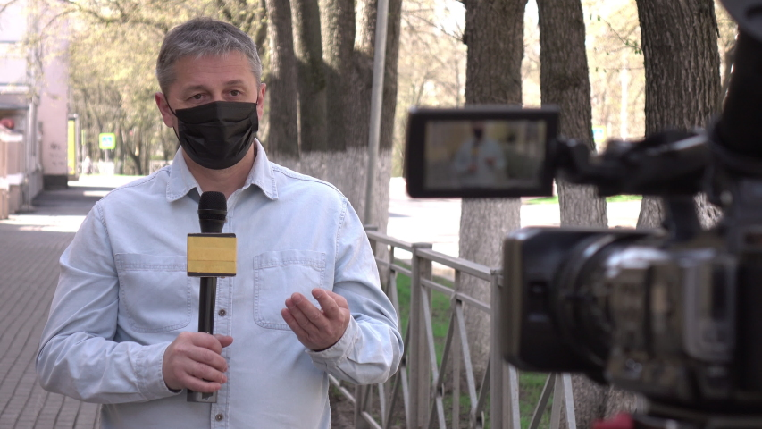 A middle- aged European journalist in a protective medical mask is reporting in a deserted city. Concept of protection against dangerous coronavirus. Report on the epidemic. | Shutterstock HD Video #1052150008