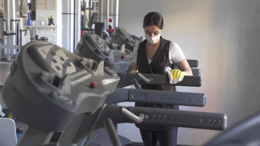 woman worker disinfects gym fitness equipment from coronavirus covid-19 with antibacterial sanitizer sprayer on quarantine. Cleaner in protective mask cleans training apparatus at workout area.  Royalty-Free Stock Footage #1052159035