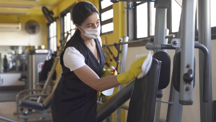 woman worker disinfects gym fitness equipment from coronavirus covid-19 with antibacterial sanitizer sprayer on quarantine. Cleaner in protective mask cleans training apparatus at workout area.  Royalty-Free Stock Footage #1052159173