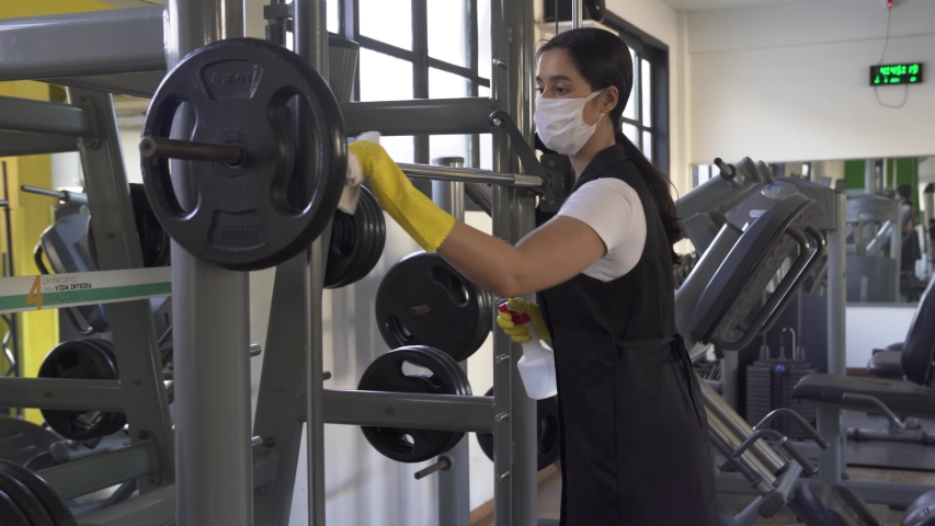woman worker disinfects gym fitness equipment from coronavirus covid-19 with antibacterial sanitizer sprayer on quarantine. Cleaner in protective mask cleans training apparatus at workout area.  Royalty-Free Stock Footage #1052159176