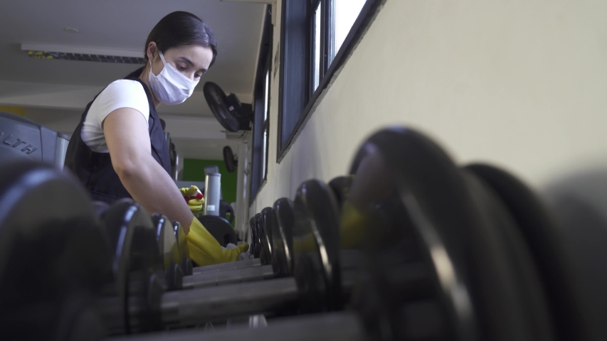 woman worker disinfects gym fitness equipment from coronavirus covid-19 with antibacterial sanitizer sprayer on quarantine. Cleaner in protective mask cleans training apparatus at workout area.  Royalty-Free Stock Footage #1052159179