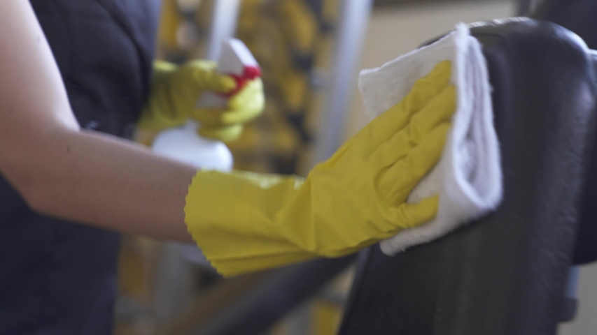 woman worker disinfects gym fitness equipment from coronavirus covid-19 with antibacterial sanitizer sprayer on quarantine. Cleaner in protective mask cleans training apparatus at workout area.  Royalty-Free Stock Footage #1052159185