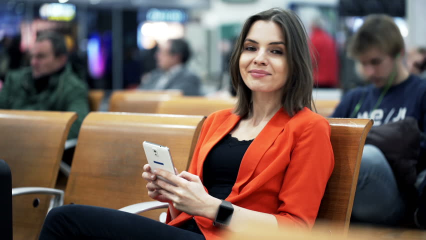 Portrait of pretty woman with smartphone sitting at train station  | Shutterstock HD Video #10521674