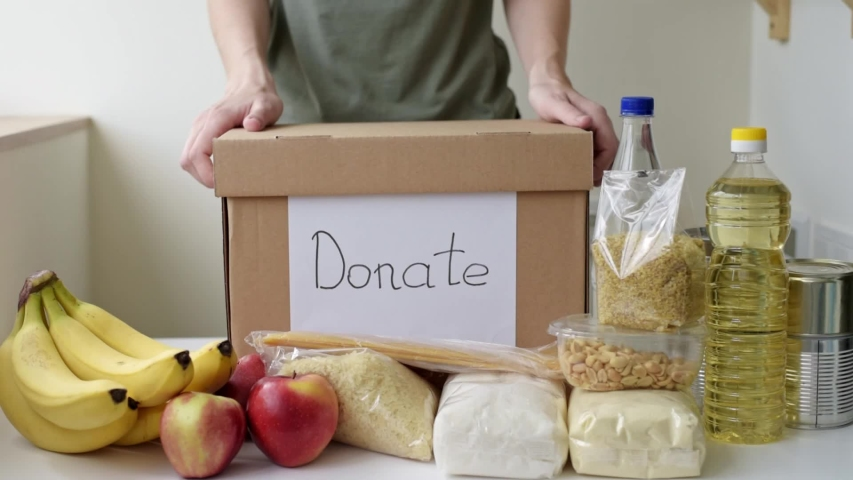 Woman puts food products in donation box. Charity and donations concept