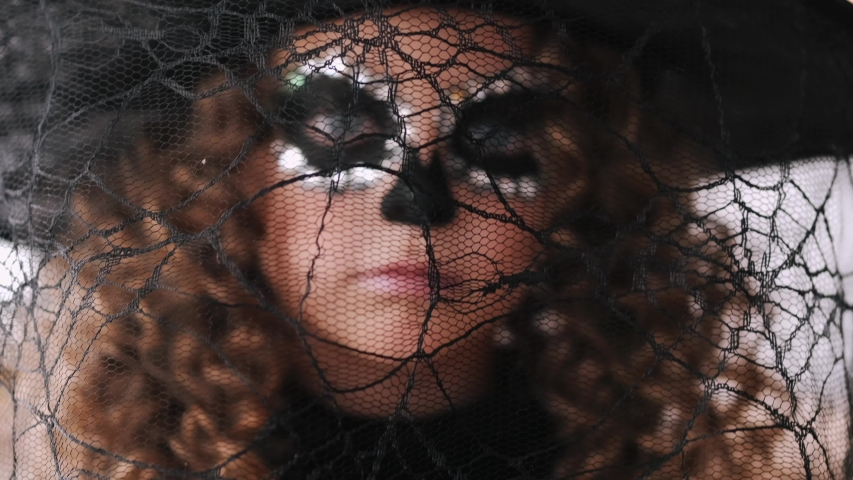 Girl wears black hat with net. Kid with curly hair has makeup. Little girl celebrates halloween.   Shutterstock HD Video #1052170906