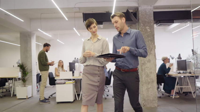 Group of businesspeople working in creative office. Interior of busy employees in a co-working space. Corporate businessmen and businesswomen sitting at desks and walking at work. Office life.