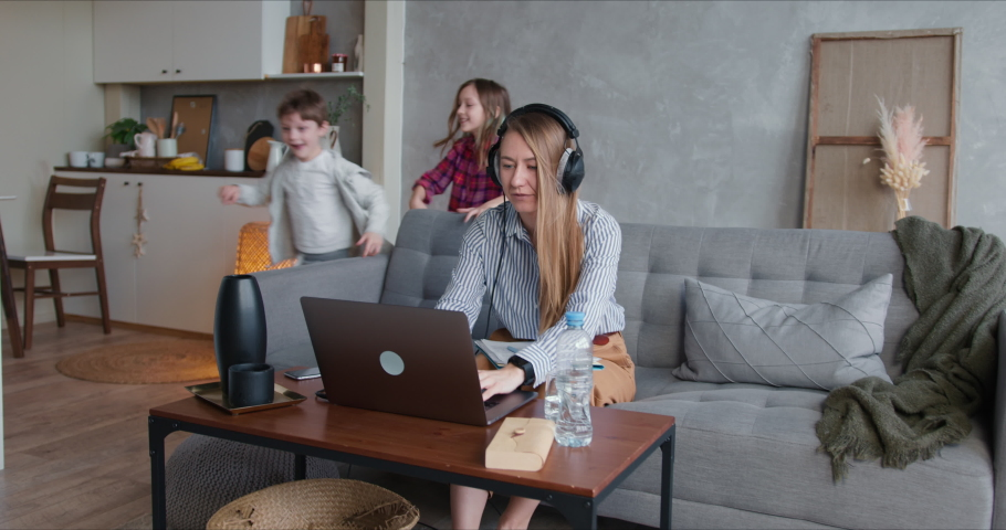Beautiful stressed single mother struggling to work from home on laptop, distracted by two noisy running teenage kids. Royalty-Free Stock Footage #1052183329