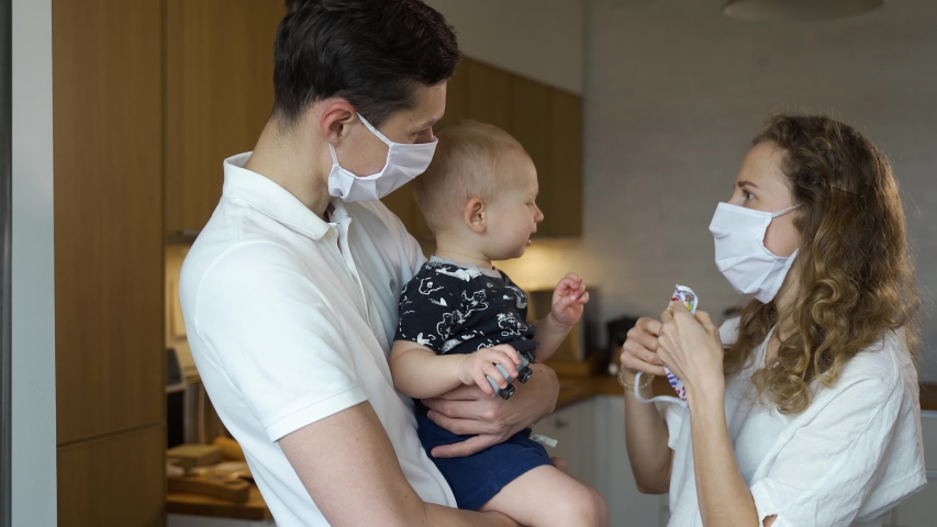 Young father and mother in masks try to put a mask on their child, the child does not like wearing mask. Family at home in quarantine during pandemic | Shutterstock HD Video #1052187034