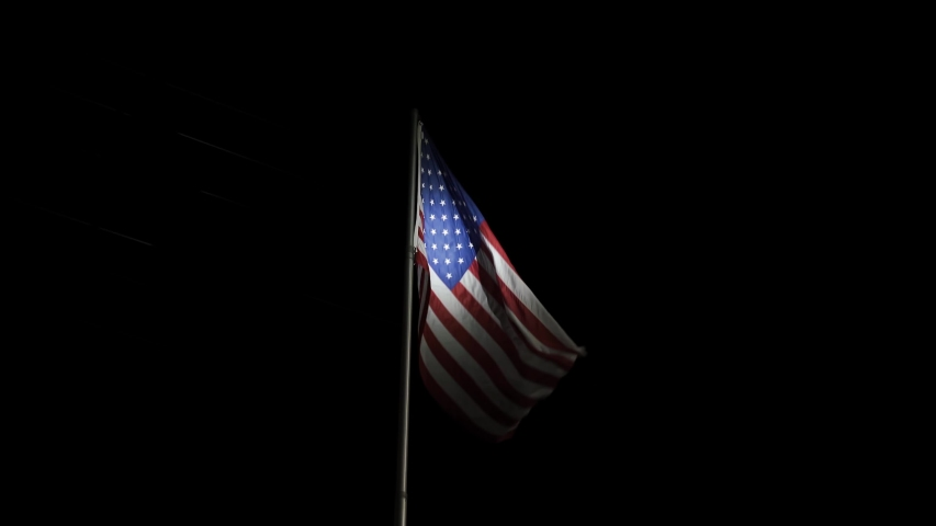 4K. the American flag at night on the flagpole flutters in the wind on independence day USA on July 4. The material of the flag of the United States of America is made of real fabric.