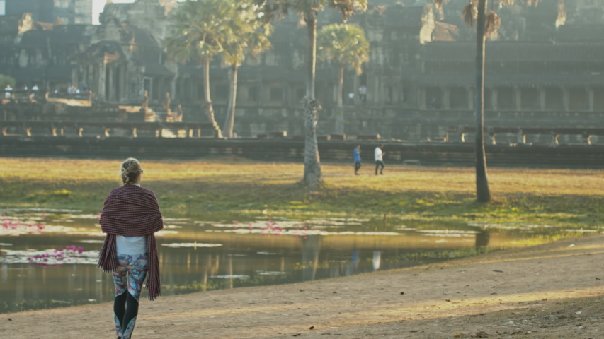 Siem Reap , Cambodia / Cambodia - 01 12 2020: Siem Reap, Cambodia, 12 January 2020 - Girl walking by the pool of the ancient Cambodian temple Angkor Wat