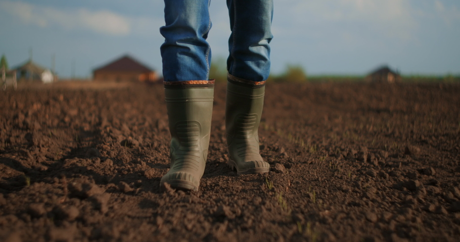 A farmer walks across a field in rubber boots on a blurred background of the tractor in motion. Concept of: Rubber boots, Lifestyle, Farmer, Slow Motion, Fields Royalty-Free Stock Footage #1052205382