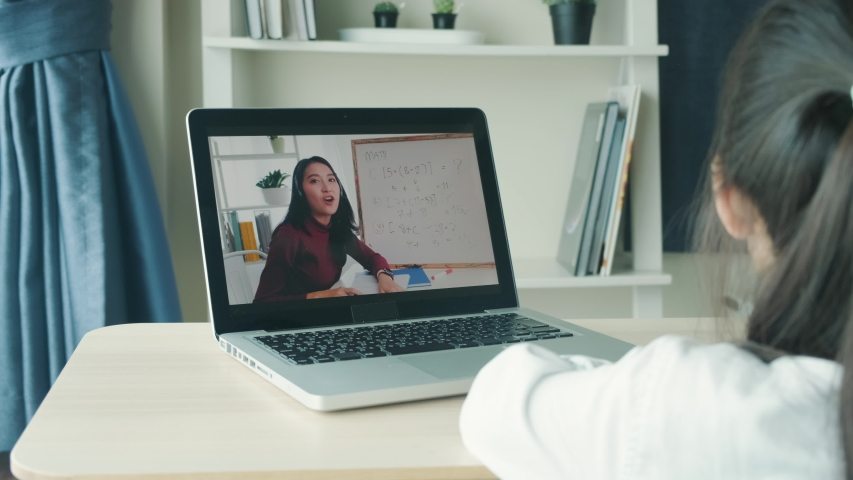 Homeschool Asian little young girl learning online education e-learning class from school teacher by conference remote meeting due to coronavirus pandemic. Student kid writing note and lecture on book   Shutterstock HD Video #1052208076