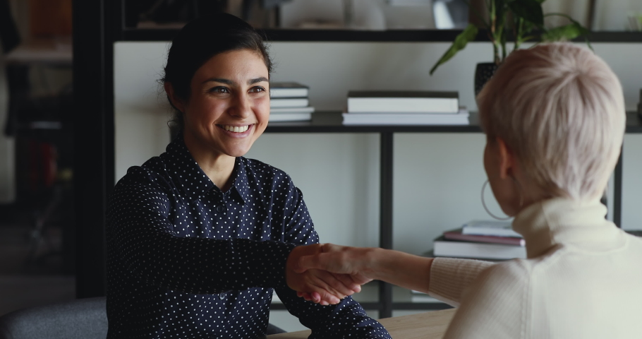 Happy confident indian recruit handshaking employer getting hired at new job. Smiling young female professional manager shake hand of woman client or customer making business deal at office meeting.