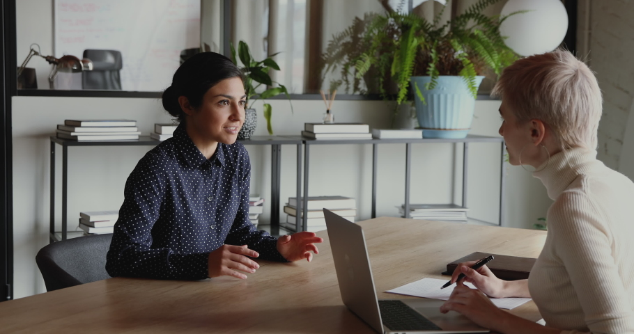Young indian female applicant talking to company recruiter at job interview. Millennial graduate candidate speaking to employer explaining professional skills at office meeting. Recruiting concept Royalty-Free Stock Footage #1052221192
