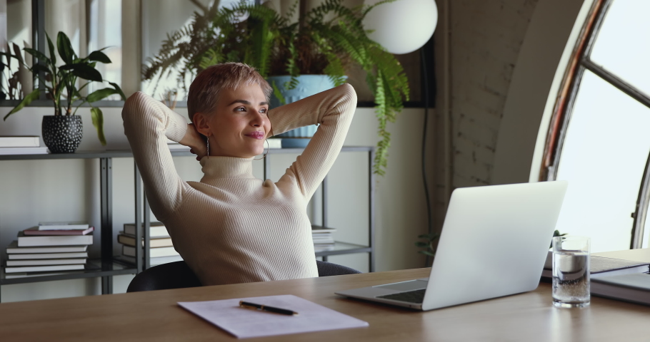 Smiling satisfied young business woman finished computer work stretching sitting at workplace desk. Happy relaxed businesswoman feeling stress relief after job well done putting hands behind head. Royalty-Free Stock Footage #1052221288