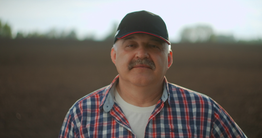 Portrait of the thoughtful senior farmer looks at camera. Senior Farmer smiling. Slow motion. Close up of the Caucasian good looking young man with a beard smiling to the camera | Shutterstock HD Video #1052224321