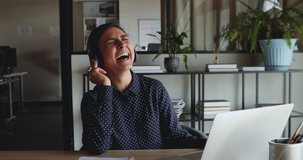 Cheerful young indian business woman wearing headphones laughing at workplace. Funny female office worker having fun listening podcast, video calling, working or studying from home office on laptop.