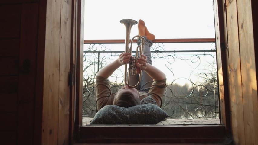 A man plays a trumpet on the balcony. there's a pillow under your head, feet up. freelancing and idleness during the pandemic. freedom of expression.